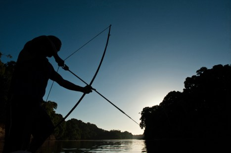 An indigenous man readies his bow and arrow. Photo by indigenous person photographer Pete Oxford.
