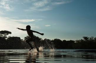 A Macushi child is silhouetted while running through water. Photograph by conservation photographer and cultural photographer Pete Oxford.