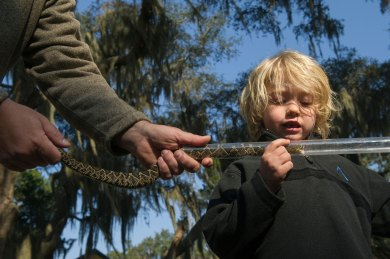 A child holds a tube while an eastern diamondback rattlesnake is put into it. Photo by conservation photographer Pete Oxford.