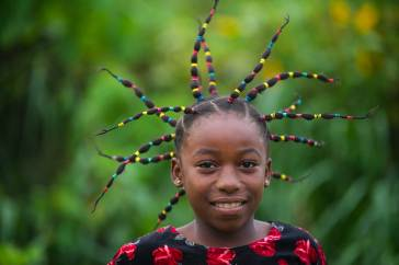 A girl from a Mbomo village shows off her hair style. Photograph by conservation photographer and cultural photographer Pete Oxford.