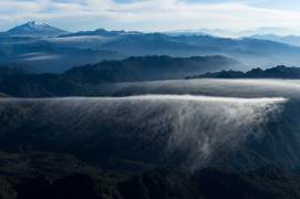 Cayambe volcano in Ecuador is shown in the distance past numerous mountains and valleys. Photograph by aerial photographer and conservation photographer Pete Oxford.