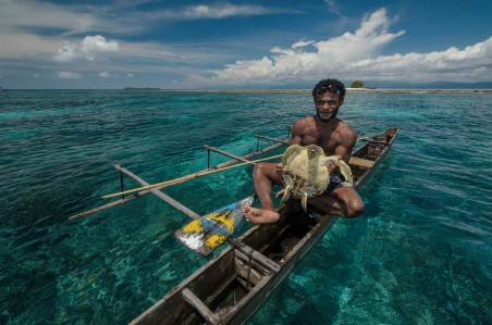 A local Papuan fisherman displays the hawksbill turtle he caught. Photo by conservation photographer Pete Oxford.