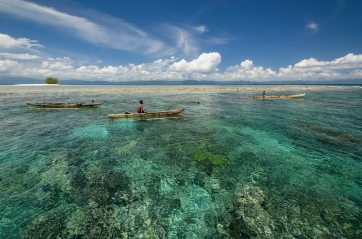 Local Papuan fisherman sit and wait in their wooden canoes. Photo by travel photographer and conservation photographer Pete Oxford.