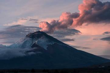 Cotopaxi volcano erupts beneath a pink sky. Photo by conservation photographer and landscape photographer Pete Oxford.