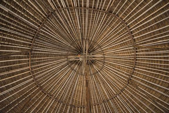 A man looks down from the rafters of the Amerindian Community Centre in Guyana. Photo by conservation photographer and cultural photographer Pete Oxford.