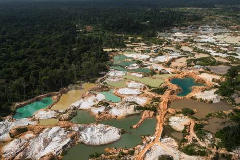 Ponds of different color water are shown with roadways between them on a gold mining site. Photo by conservation photographer Pete Oxford.