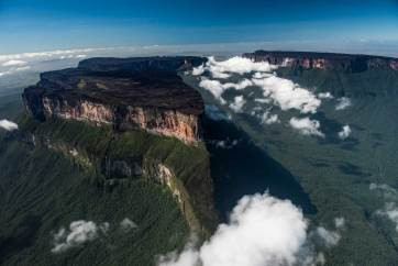 Mount Roraima is flanked by clouds as it casts a shadow over the surrounding forest. Photograph by aerial photographer and conservation photographer Pete Oxford.