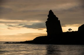 Pinnacle Rock is silhouetted against a rising sun in the Galapagos Islands. Photo by landscape photographer Pete Oxford.