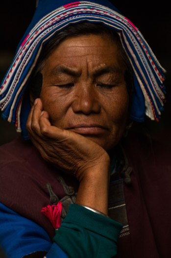 A Bai woman rests with the palm of her hand under her chin. Photo by indigenous person photographer Pete Oxford.