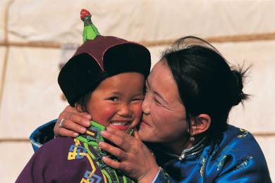 A tender moment is shared between mother and child Gobi Nomads. Photograph by conservation photographer and cultural photographer Pete Oxford.