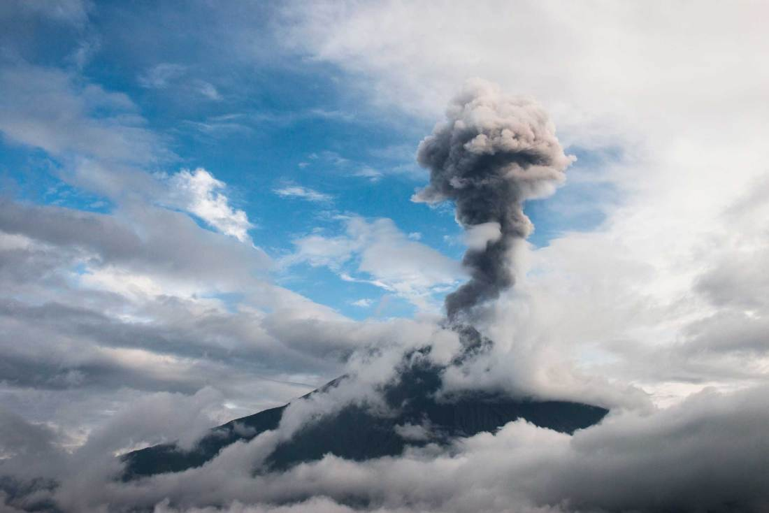Tungurahua Volcano erupts, releasing an ash and gas cloud into the sky.