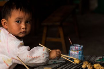 A child looks to the camera while reaching for food with chopstix. Photo by indigenous person photographer Pete Oxford.