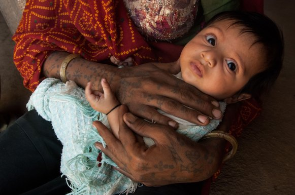 A Rabari woman holds a child in her hands. Photo by indigenous person photographer Pete Oxford.