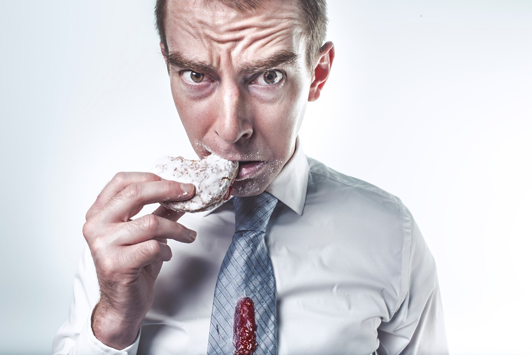 man eating a donut as a cheat meal