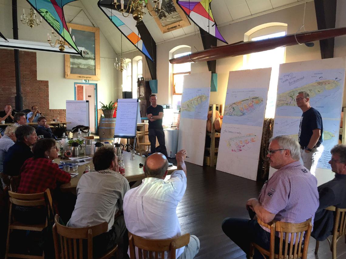 Peter de Ruyter staat voor een groep toehoorders over plannen voor de Boschplaat op Terschelling.