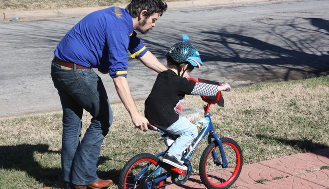 Man teaching child how to ride a bike