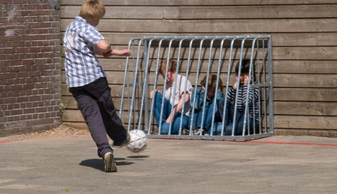 A schoolyard bully kicks a soccer ball at some younger children