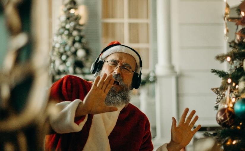 Man wearing santa claus outfit and headphones