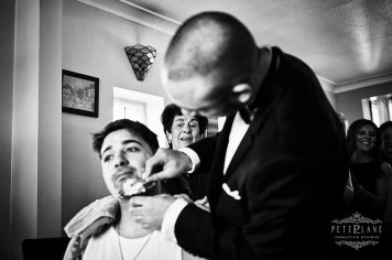 Documentary wedding photographer groom being shaved