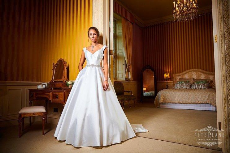 Bride posing in long elegant wedding dress