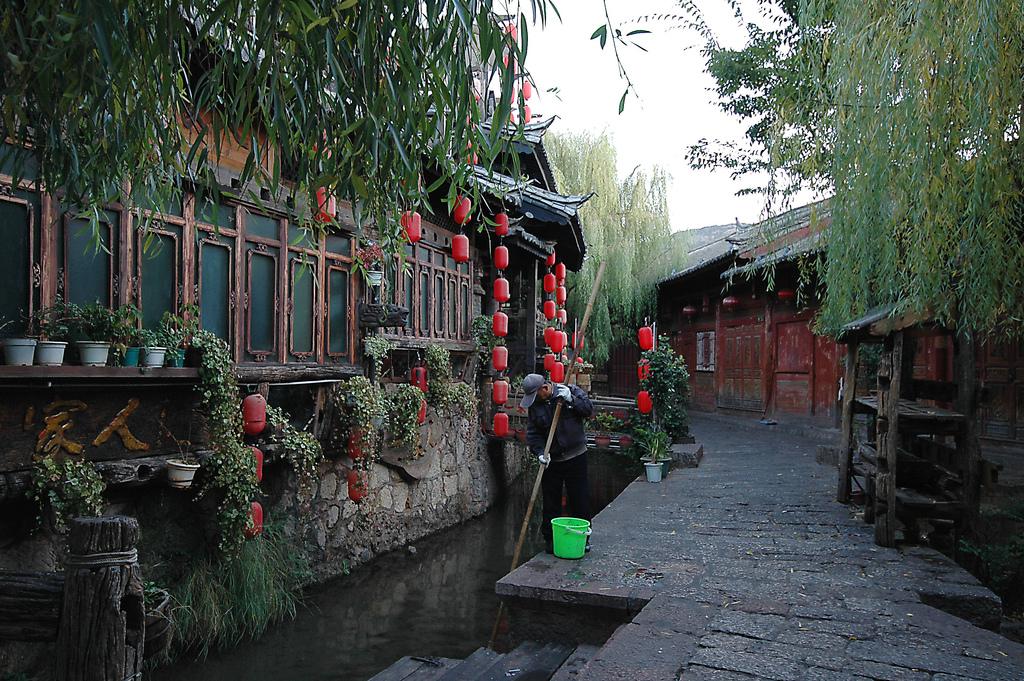 Morgonstädning av kanalerna i Lijiang, Kina.