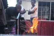 A woman lightening fire to fry fish at Gatwikera near Kamukunji grounds in Kibera slum