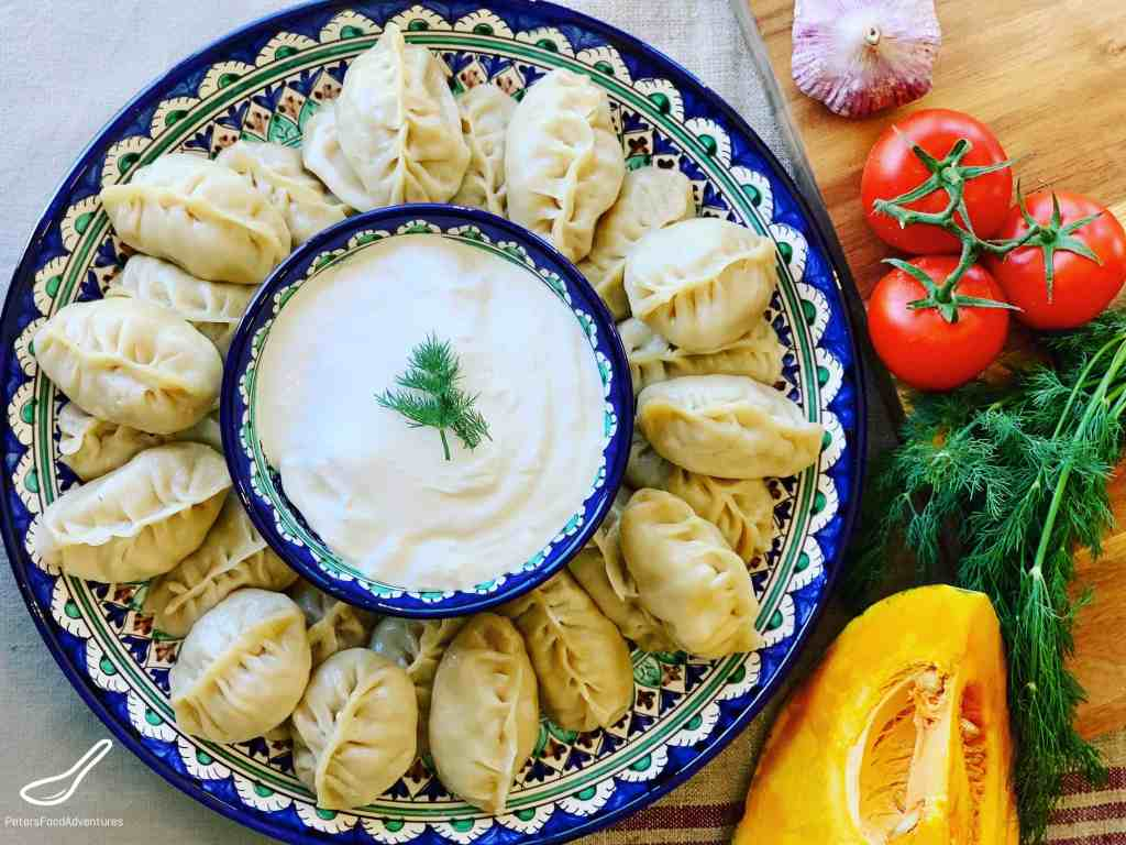 Manti (Узбекские манты) on a round Uzbek platter on a dinner table with fresh vegetables. Served with sour cream
