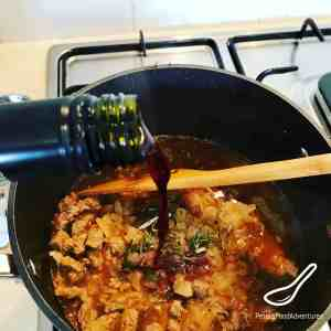 Pouring red wine into sautéed beef for a meat pie