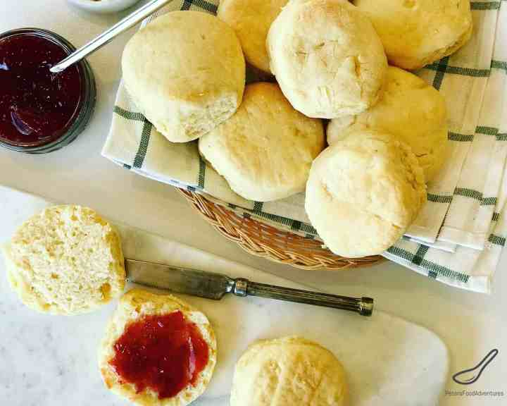 Top view of scones in a basket, spread with strawberry jam