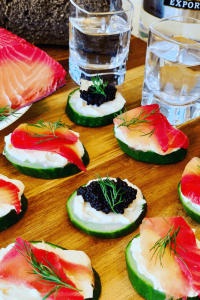 Cucumber Appetizers with caviar and salmon, on a table with 2 shots of vodka