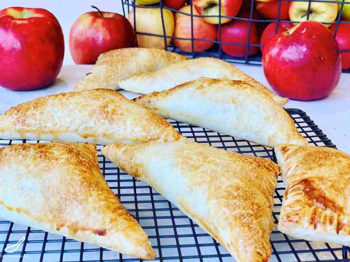 Apple Turnovers on a cooling rack with fresh apples