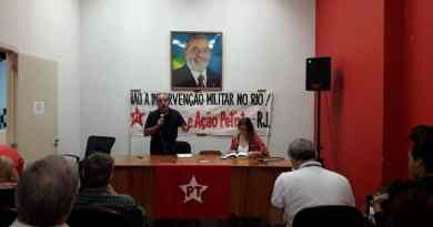 mesa do debate com foto do lula ao fundo