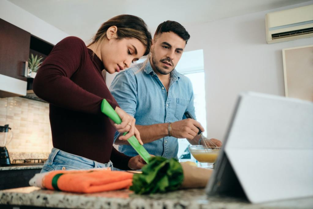 Couple Cooking Together And Watching Tutorial