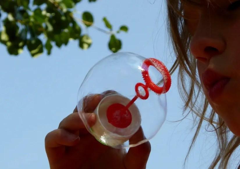 Faire des bulles de savon, un des jeux de plein air à jouer seul appréciés des tout-petits.