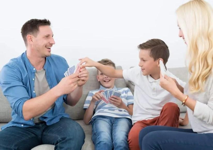 Parents et enfants s'amusent avec un jeu de cartes en famille