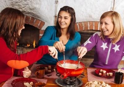 Jeunes femmes mangeant une fondue au fromage