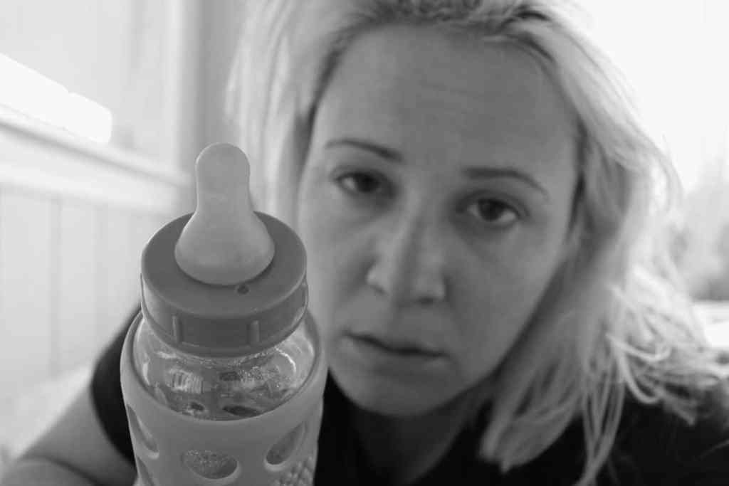 Maman à 40 ans fatiguée tendant un biberon à son bébé