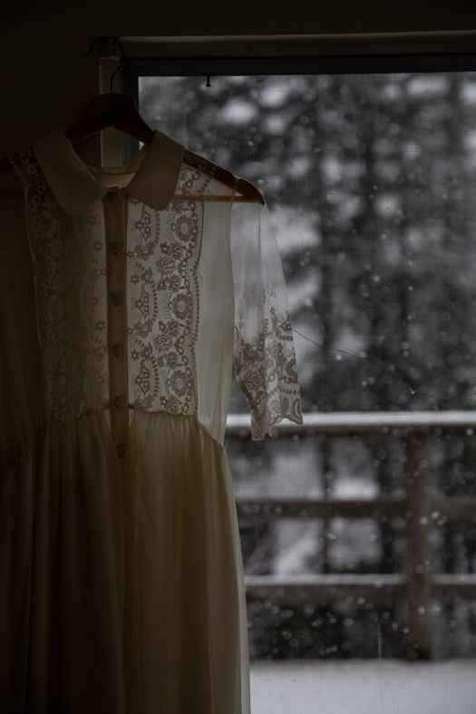 vintage dress hanging on hanger near window in rainy day
