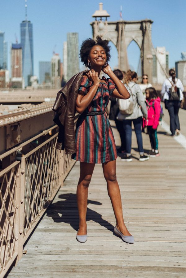Standing and smiling on the Brooklyn Bridge with the Allbirds Tree Breezers