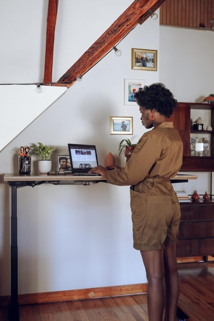 Black Women Standing at a standing desk working on a laptop