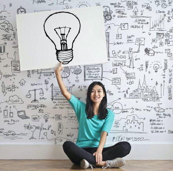 femme avec mur rempli de dessin et affiche avec ampoule