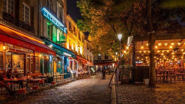 rue le soir éclairée avec devantures de brasseries parisiennes