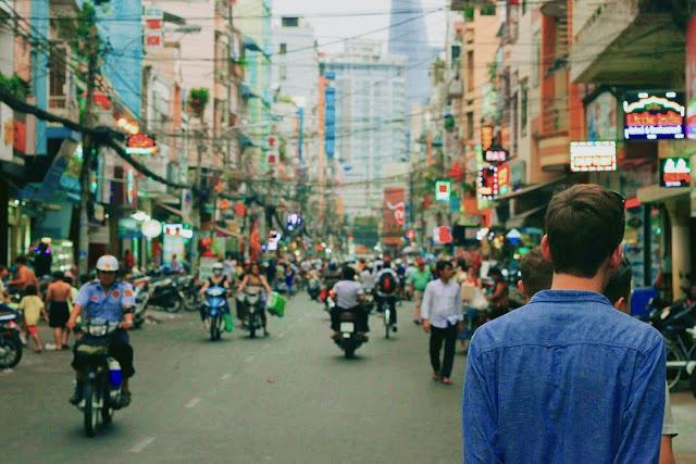 homme dans une rue animé dans un pays asiatique car slow travel permet de faire des économies sur le transport