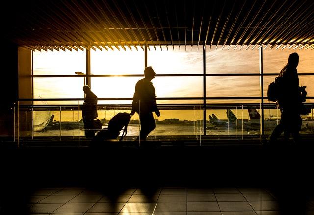 homme tenant son bagage cabine et marchant dans l'aéroport