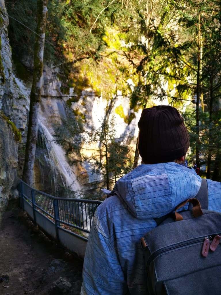 un homme avec un sac à dos qui marche vers une cascade
