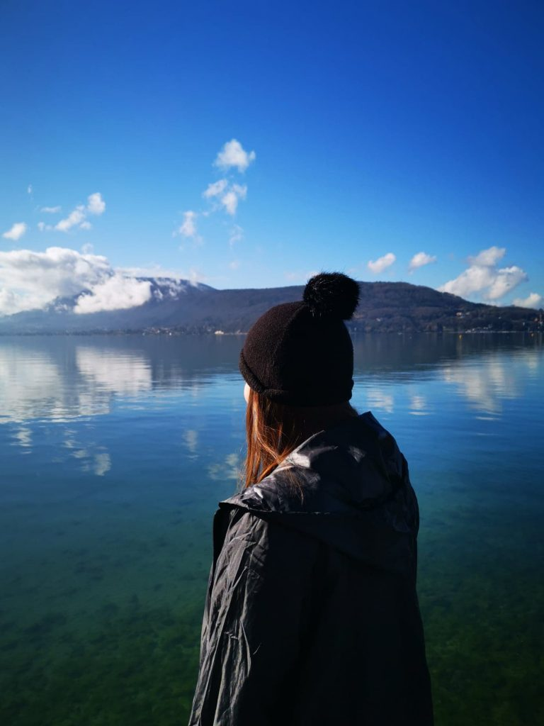 une femme qui porte un bonnet qui regarde le lac d'Annecy