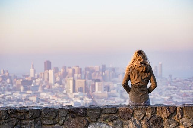femme assise sur un muret qui regarde la vue