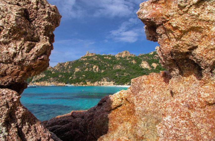 vue entre deux rochers d'une plage en corse