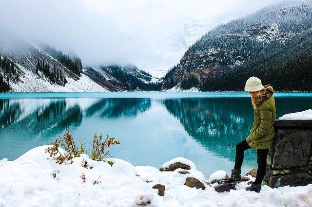 fille au bord d'un lac et d'une montagne enneigée car déterminer quand partir à quelle saison permet de choisir sa destination de voyage