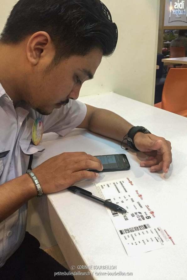 Le gars de l'aéroport vérifie mon boarding pass. (Makassar, Sulawesi, Indoénsie, juillet 2017)